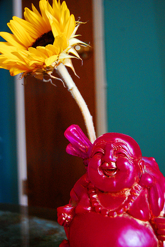 Small Laughing Buddha with flower (image via Buddha Collective)